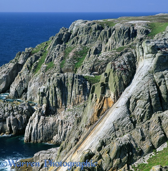 Rock climbers, dwarfed by granite cliffs.  Lundy Island, England