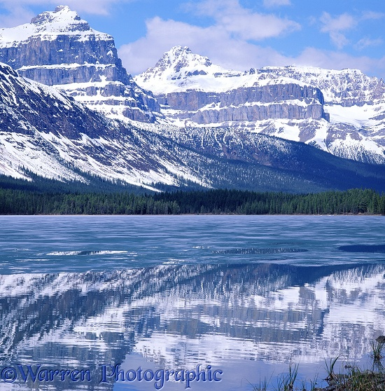 Rocky Mountains reflected in lake with ice.  Alberta, Canada