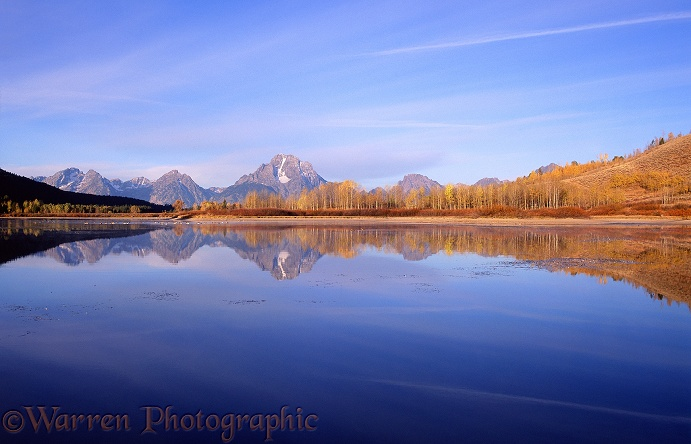 Grand Teton mountains reflected in a still lake at sunrise.  Wyoming, USA