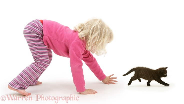 Girl chasing a black kitten