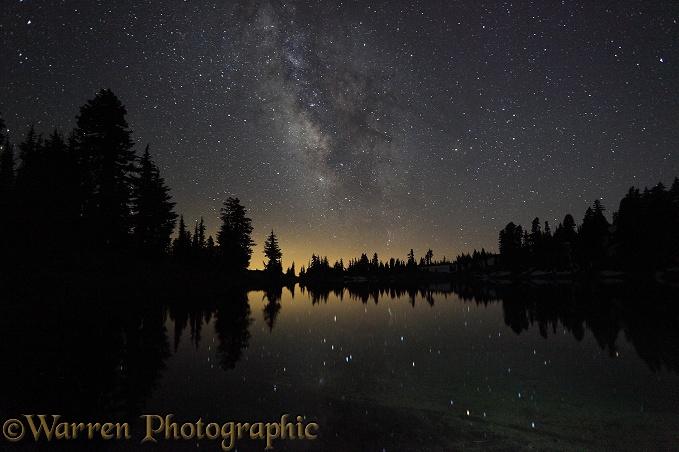 Lake with reflected stars of the Milky Way and silhouette trees.  Lassen Volcanic National Park, California