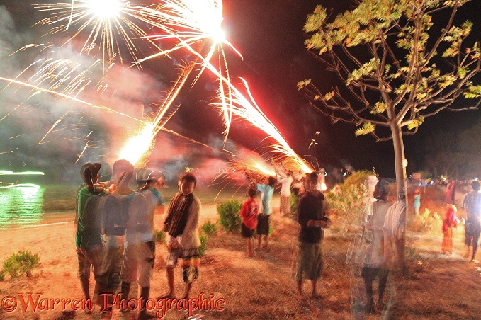 People letting off fireworks by hand for end of Ramadan celebrations.  Gili Islands, Lombok, Indonesia