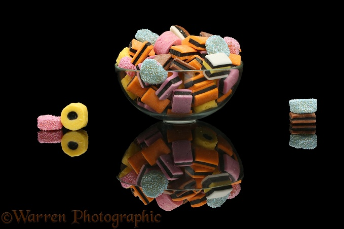 Liquorice all sorts in a glass bowl, black background