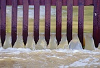 Flood water pouring through a fence