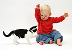 Black-and-white kitten playing with toddler