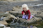 Little girl splashing water at Kimmeridge