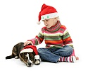 Girl and puppy both wearing Santa hats