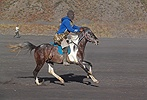 Man in balaclava galloping on a horse an Bromo