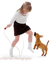 Puppy barking at girl with skipping rope