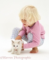 Little girl picking up a kitten