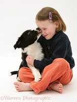 Child being licked by a puppy