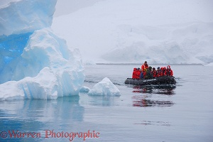 Tourists in zodiac boat viewing icebergs