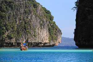 Long-tail boat and limestone cliffs