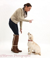 Lady instructing a dog to sit