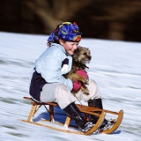 Girl tobogganing with a dog