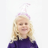 Little girl (5) with birthday party hat on